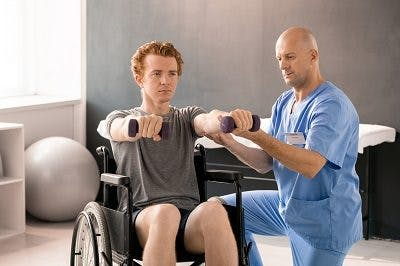 adult male with cerebral palsy participating in physical therapy