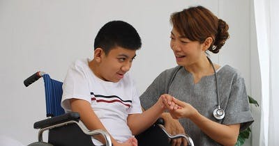 A physical therapist is talking to a disabled boy with severe cerebral palsy in a wheelchair.