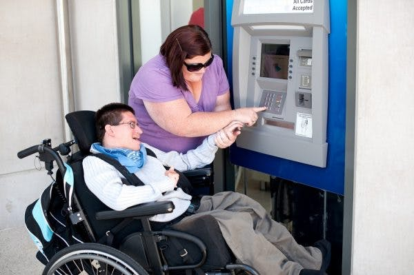 A young man with severe cerebral palsy in a wheelchair being assisted to use an ATM.