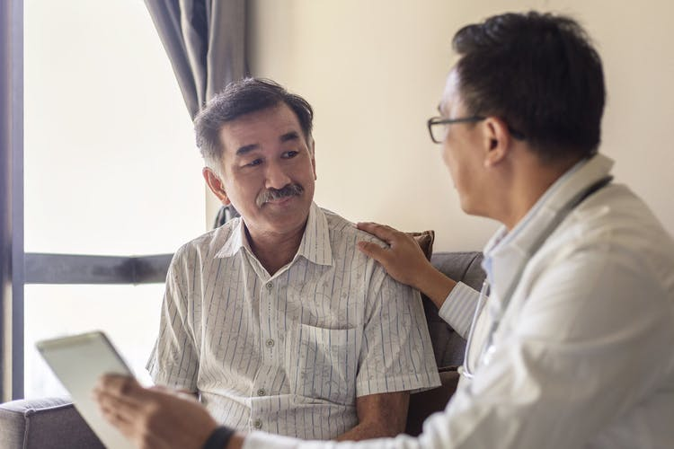 doctor talking to patient with agnosia holding up tablet