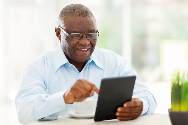homme âgé faisant des exercices de rééducation cognitive sur tablette pour améliorer la mémoire après un AVC