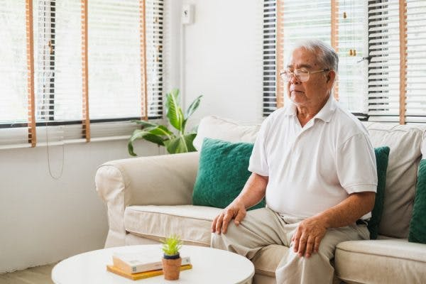 stroke survivor sitting on a couch with eyes closed doing mental practice